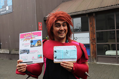 Description: A man looking at the camera, smiling. He is holding a clipboard with Fringe raffle tickets on one hand, and a sheet that shows the Raffle prizes in another. Caption: Our Raffle Coordinator gets to dress up every day! Photo by Al Ricard.